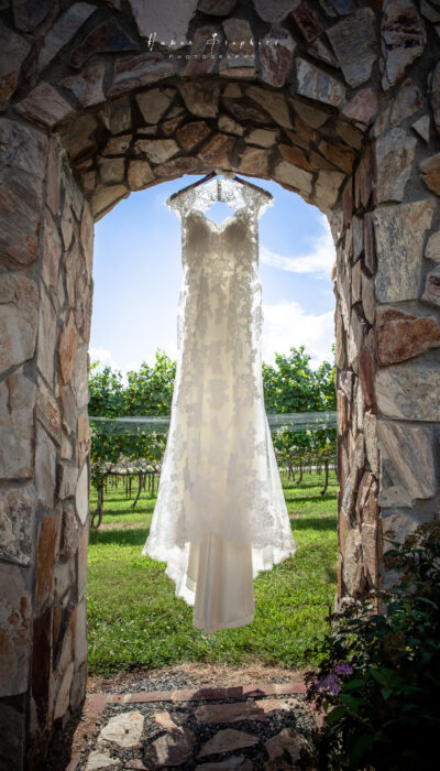 Wedding dress hanging from a stone entrance with Vineyard views at Parker-Binns Vineyard in Mill Spring, NC